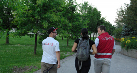 An image of two goSAFE members walking a student to class.